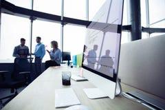 Конец-вверх рабочего места в современном офисе с бизнесменами позади Коллеги встречая для того чтобы обсудить их будущее финансов стоковые фотографии rf
