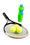 Конец-вверх ракетки, шариков и бутылки тенниса воды на белой предпосылке Стоковые Фото