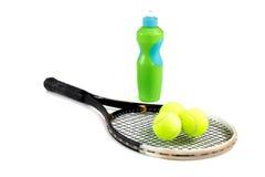 Конец-вверх ракетки, шариков и бутылки тенниса воды на белой предпосылке Стоковые Изображения