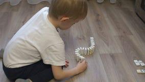 Конец-вверх ребенка играя с домино дома на поле видеоматериал