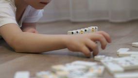 Конец-вверх ребенка играя с домино дома на поле сток-видео