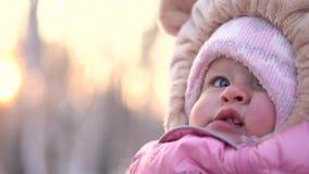 Конец-вверх ребенка усмехаясь в зиме Счастливый любопытный ребенок в розовом комбинезоне в предпосылке зимы парка видеоматериал