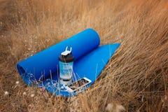Конец-вверх резвится детали Циновка, бутылка воды и телефон на естественной предпосылке Outdoors тренируя концепция скопируйте ко Стоковое Фото