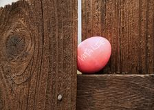 Конец вверх розов-покрашенного пасхального яйца с именем ` Натали ` спрятан на уступе на деревянной загородке Стоковое фото RF