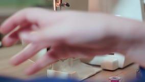 Конец-вверх, руки белошвейки принимает вне продевает нитку для катушкы движение медленное сток-видео