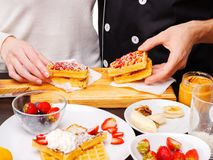 Конец-вверх руки девушки и парня которая принимают бельгийские waffles от деревянной доски, на таблице различные плодоовощи Стоковые Изображения