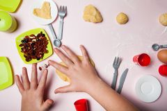 Конец-вверх, руки детей замешивает тесто Детские игры в делать печенье дома стоковая фотография rf