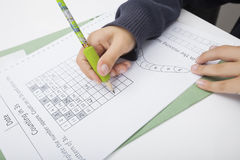 Конец-вверх руки девушки писать номера на бумаге Стоковая Фотография