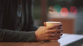 Конец-вверх руки женщины s держа чашку кофе, перегар от чашки чая Запачканные света, городская улица видеоматериал