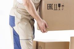 Конец-вверх руки затяжелителя держа картонную коробку изолированный на белой предпосылке Затяжелитель выбирает вверх коробку Движ Стоковое Изображение RF