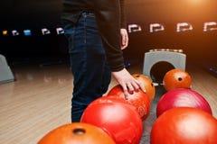 Конец вверх руки игрока боулинга принимая красный шарик от подъема шара Стоковая Фотография