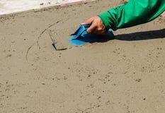 Конец-вверх руки используя лопатку для того чтобы закончить влажный конкретный пол Стоковое Фото