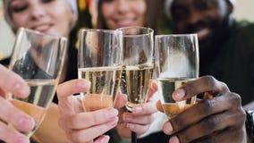 Конец-вверх руки людей различных гонок которые держат бокалы игристого вина пузыри в бокалах с сток-видео