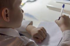 Конец-вверх руки мальчика при карандаш писать английские слова вручную на традиционной белой бумаге блокнота Стоковое Фото