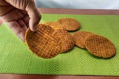 Конец-вверх руки устанавливая stroopwafel на таблице стоковые фото
