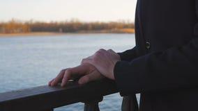 Конец-вверх руки человека который стоит около реки, царапая на перилах весной выравниваясь сток-видео