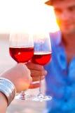 Конец-вверх руки 2 human's с вином рюмок красным во время Стоковое фото RF
