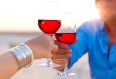 Конец-вверх руки 2 human's с вином рюмок красным во время Стоковые Изображения RF