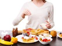 Конец-вверх руки ` s девушки брызгает с напудренными waffles сахара бельгийскими с завалкой банана Стоковые Фото