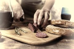 Конец вверх руки ` s персоны отрезал салями на доске кухни влияние кино Стоковые Изображения RF