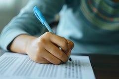 Конец вверх руки ` s студента держит ручку пишет на листе ответа Студент отвечает на вопросы о разнообразного выбора на деревянно стоковые изображения