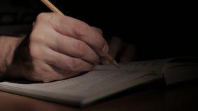 Конец-вверх руки ` s человека с открытой бумажной книгой, пишет примечание с карандашем на странице сток-видео