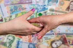 конец вверх Рукопожатия женщин на предпосылке денег Стоковое фото RF