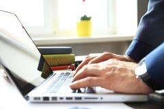 Конец-вверх рук бизнесмена используя кнопочную панель компьтер-книжки Стоковое Изображение