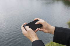 Конец-вверх рук бизнесмена отправляя СМС на умном телефоне вдоль реки Стоковое Изображение