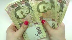 Конец-вверх рук бизнесмена подсчитывая 100 счетов hryvnia на таблице сток-видео