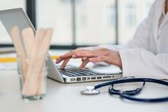 Конец-вверх рук врача печатая на компьтер-книжке в  Стоковые Фото