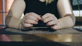 Конец-вверх рук девушки на таблице в кафе Девушка в ожидании заказ вытягивает волосы рук эластичные сток-видео