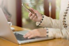 Конец-вверх рук женщины используя умные телефон и компьтер-книжку стоковая фотография