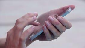 Конец-вверх рук женщины при славный маникюр отправляя СМС, послание на умном телефоне видеоматериал
