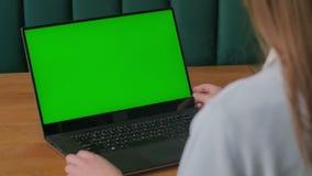 Конец-вверх рук женщины работая на зеленом экране на ноутбуке E акции видеоматериалы