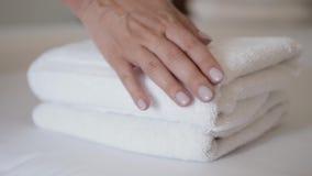 Конец-вверх рук кладя стог свежих белых полотенец ванны на простыню Макрос гостиничного номера чистки горничной гостиничного серв акции видеоматериалы