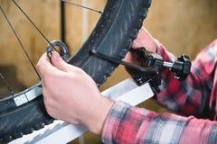 Конец-вверх рук людей со специализированным ключем на стойке в мастерской затягивая спицы колеса стоковое изображение rf