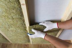 Конец-вверх рук работника в белых перчатках изолируя шерсти утеса внутри Стоковое Фото