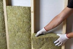 Конец-вверх рук работника в белых перчатках изолируя шерсти утеса внутри Стоковая Фотография