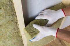 Конец-вверх рук работника в белых перчатках изолируя шерсти утеса внутри Стоковое Изображение