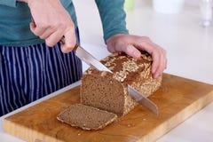 Закройте вверх рук режа ломтик хлеба Стоковое Фото