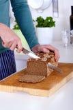 Закройте вверх рук режа ломтик хлеба Стоковая Фотография