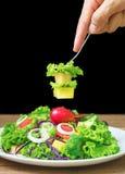 Конец-вверх рук с салатом дегустации вилки Стоковые Изображения RF