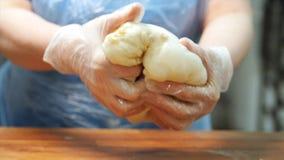 Конец-вверх рук хлебопека в перчатках силикона замешивая часть теста для того чтобы сделать некоторые хлебобулочные изделия r стоковые фото