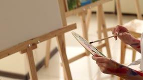 Конец-вверх рук художника грязных с краской с палитрой и щеткой сток-видео