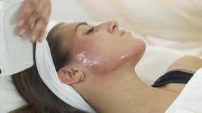 Конец вверх рук cosmetologist положил воск на щеки, подбородок девушки в салоне красоты сток-видео