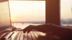 Конец вверх рук ` s женщины печатая на клавиатуре ` s компьтер-книжки во время красивого захода солнца с влияниями пирофакела len Стоковые Изображения