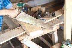 Конец-вверх рук ` s женщин с досками sawing hacksaw, плотничество мастерское стоковые фото