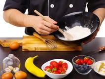Конец-вверх рук ` s шеф-повара в рисберме, замешивает тесто в шаре стоковое изображение