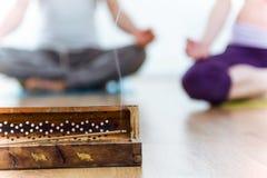 Конец-вверх ручки ладана, за парами делая йогу Стоковые Фотографии RF